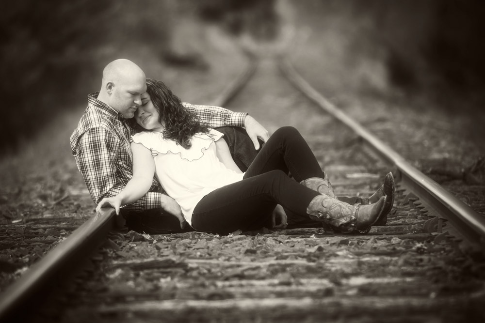 engaged couple on railroad tracks