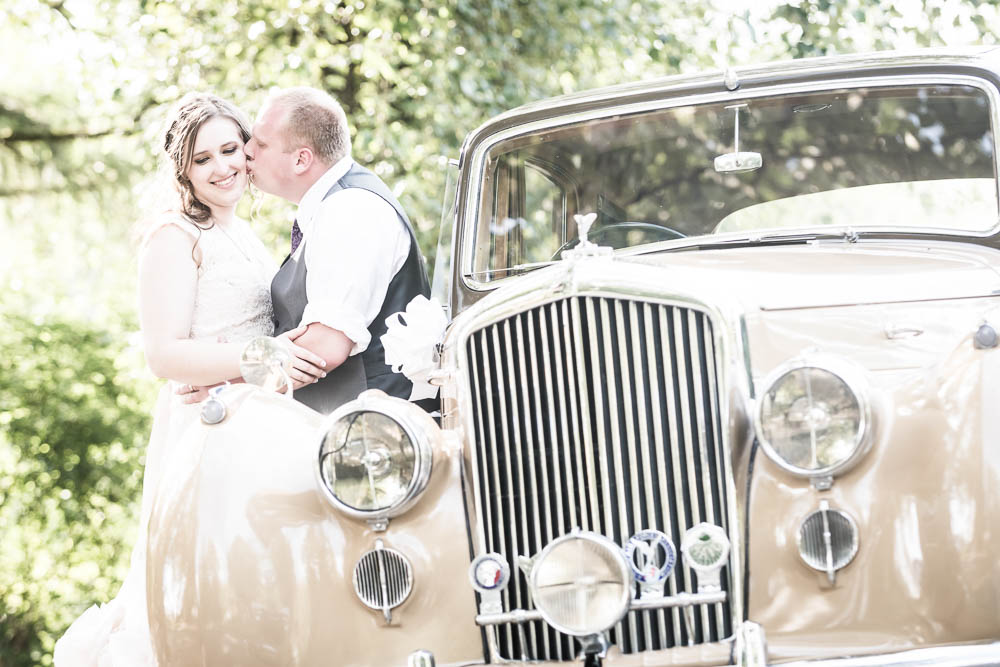 groom kissing bride by old car